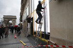 Workers set up protection on shop windows the Champs-Elysees avenue, Friday, Dec. 7, 2018 in Paris. Many shop owners across the French capital are getting ready for the violence, setting up walls with carton boards to protect their windows. (AP Photo/Francois Mori)