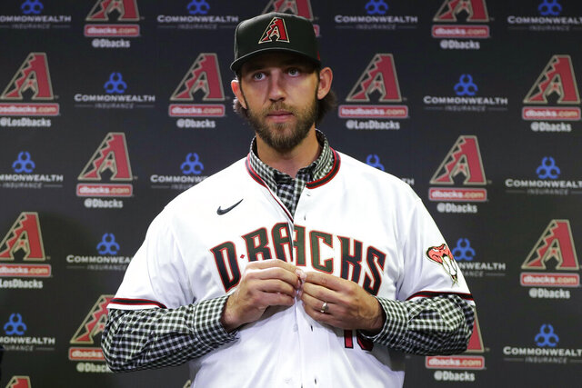 FILE - In this Dec. 17, 2019, file photo, newly acquired Arizona Diamondbacks pitcher Madison Bumgarner puts on a jersey after being introduced during a team availability in Phoenix. The Diamondbacks added a handful of veteran free agents during the offseason, including Bumgarner, outfielder Kole Calhoun, catcher Stephen Vogt and reliever Héctor Rondón. The left-handed Bumgarner — a four-time All-Star and 2014 World Series MVP — was the marquee signing, joining the rotation on an $85 million, five-year deal. (AP Photo/Matt York, File)