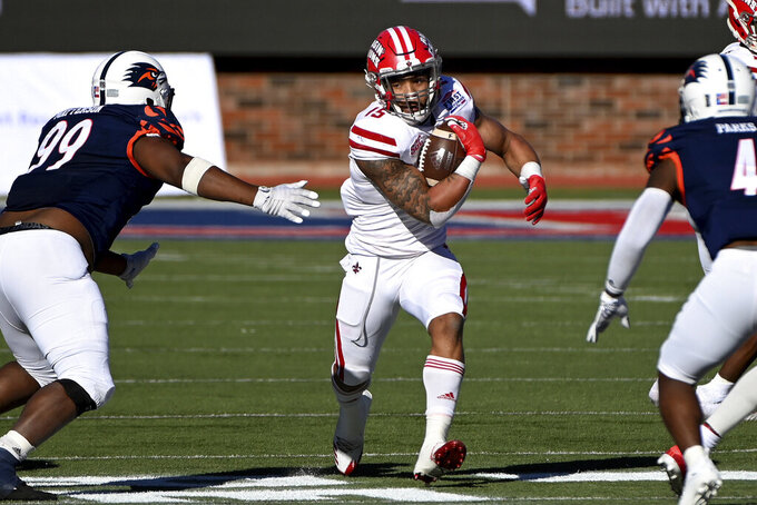 Louisiana-Lafayette running back Elijah Mitchell (15) runs between UTSA defensive lineman Brandon Matterson (99) and safety Antonio Parks (4) during the first quarter during the First Responder Bowl NCAA college football game in Dallas, Saturday, Dec. 26, 2020. (AP Photo/Matt Strasen)