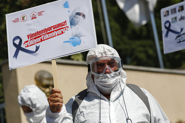 A health worker wearing personal protective equipment holds a protest against the Turkish goverment's health policy in front of Istanbul University medical faculty, Tuesday, Sept. 15, 2020. Amid surging numbers of COVID-19 deaths and cases in the country, the Turkish Medical Association (TTB) had called out and urge the authorities to step up measures. The placard reads in Turkish: