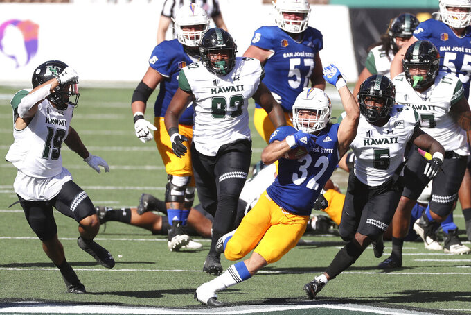 San Jose State running back Kairee Robinson (32) squeezes through the Hawaii defense in the first half of an NCAA college football game Saturday, Dec. 5, 2020, in Honolulu. (AP Photo/Marco Garcia)