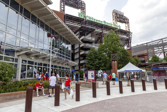 Fans gather at the gate of Citizens Bank Park after the baseball game between the Philadelphia Phillies and the Washington Nationals was suspended due to COVID-19 issues among the Nationals, Wednesday, July 28, 2021, in Philadelphia. (AP Photo/Laurence Kesterson)