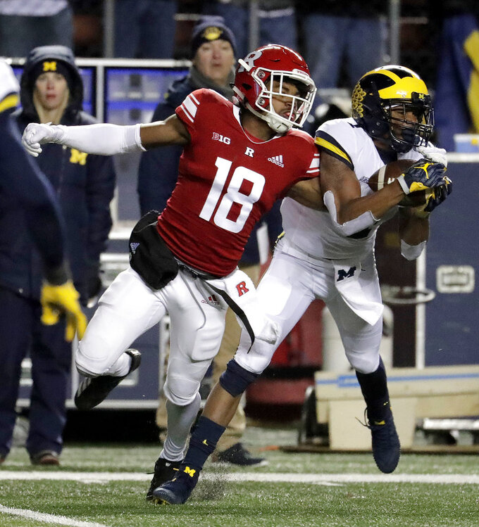 Michigan defensive back Ambry Thomas, right, intercepts a pass from Rutgers quarterback Artur Sitkowski which was intended for wide receiver Bo Melton, left, during the second half of an NCAA college football game, Saturday, Nov. 10, 2018, in Piscataway, N.J. (AP Photo/Julio Cortez)