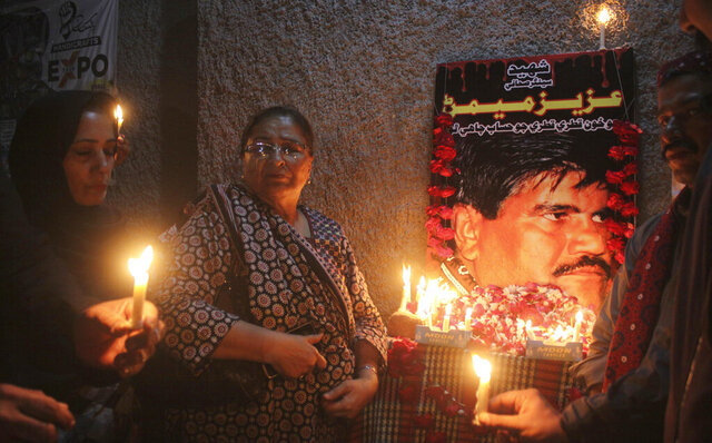 In this Oct. 17, 2020, photo, Pakistani civil society activists hold candle vigil to pay tribute to Aziz Memon in Hyderabad, Pakistan. In Pakistan, being a dissident or even raising a critical voice is dangerous business. Rights groups say that despite the election in 2018 of a civilian government, the army still rules from behind with an iron fist. (AP Photo/Pervez Masih)