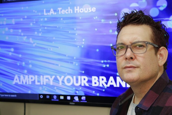 In this Tuesday, Sept. 17, 2019 photo, Gabe Uribe, co-owner of L.A. Tech House, a public relations firm that focuses on tech companies, poses in his office in Beverly Hills, Calif. When he began advertising online, he went with the common wisdom that the more spent on Google ads, the better the results. But he learned he could cut his budget and be fine.