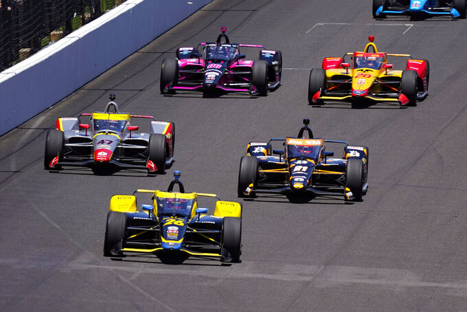 Colton Herta (26) leads Rinus VeeKay (21), of the Netherlands, and Conor Daly (47) into the first turn during the Indianapolis 500 auto race at Indianapolis Motor Speedway in Indianapolis, Sunday, May 30, 2021. (AP Photo/Paul Sancya)