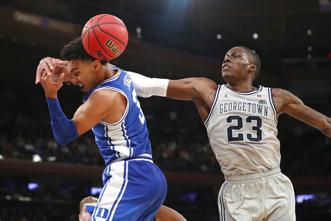 Georgetown forward Josh LeBlanc (23) knocks the ball away from Duke guard Tre Jones (3) during the second half of an NCAA college basketball game in the 2K Empire Classic, Friday, Nov. 22, 2019 in New York. Duke won 81-73. (AP Photo/Kathy Willens)