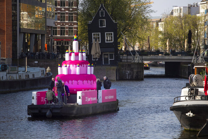 A huge inflatable pink cake with candles spouting rainbow flames glided through the Amsterdam canals Thursday as the Dutch capital celebrated the 20th anniversary of the world's first legal same-sex marriages, Thursday, April 1, 2021. Twenty years ago, the mayor of Amsterdam married four couples in City Hall as the Netherlands became the first country in the world with legalized same-sex marriage. It's now legal in 28 countries. (AP Photo/Peter Dejong)