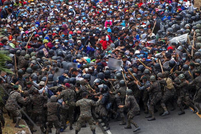 Honduran migrants clash with Guatemalan soldiers in Vado Hondo, Guatemala, Sunday, Jan. 17, 2021. Guatemalan authorities estimated that as many as 9,000 Honduran migrants crossed into Guatemala as part of an effort to form a new caravan to reach the U.S. border. (AP Photo/Sandra Sebastian)