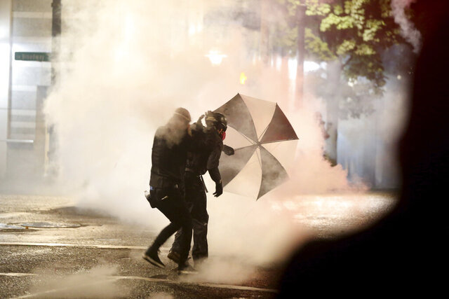 Protesters demanding the end of police violence against Black people take cover from smoke during a demonstration in Portland, Ore., on Wednesday, Sept. 23, 2020. Protesters in Portland hurled Molotov cocktails at officers in Oregon's largest city during a demonstration over a Kentucky grand jury's decision to not indict officers in the fatal shooting of Breonna Taylor, police said Thursday. (Mark Graves/The Oregonian via AP)