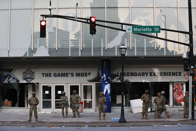 The Georgia National Guard lines up in front of the of the College Football Hall of Fame in the aftermath of a demonstration against police violence on Saturday, May 30, 2020, in Atlanta. (AP Photo/Brynn Anderson)
