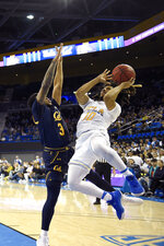 UCLA guard Tyger Campbell, right, shoots as California guard Paris Austin defends during the first half of an NCAA college basketball game Sunday, Jan. 19, 2020, in Los Angeles. (AP Photo/Mark J. Terrill)
