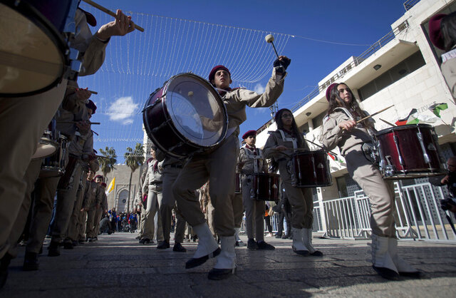 A Palestinian Scout marching band parades during Christmas celebrations outside the Church of the Nativity, built atop the site where Christians believe Jesus Christ was born, on Christmas Eve, in the West Bank City of Bethlehem, Tuesday, Dec. 24, 2019. (AP Photo/Majdi Mohammed)
