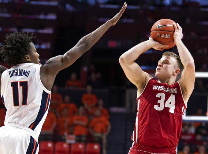 File-This Jan. 23, 2019, file photo shows Wisconsin guard Brad Davison (34) shooting over Illinois guard Ayo Dosunmu (11) during the second half of an NCAA college basketball game in Champaign, Ill. Davison, Wisconsin's second-leading returning scorer (10.5 points per game) is expected to help along with D'Mitrik Trice. Trice, 6-foot junior, could emerge as Wisconsin's top scoring option this year after averaging 11.6 points last season.  (AP Photo/Stephen Haas, File)