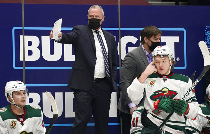 Minnesota Wild coach Dean Evason, back, directs the team during the third period of an NHL hockey game against the Colorado Avalanche on Tuesday, Feb. 2, 2021, in Denver. (AP Photo/David Zalubowski)