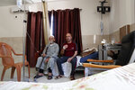 In this Tuesday, June 16, 2020 photo. Palestinian cancer patient Jehad al-Qedra, 52, and his relative Jabr, sit on the bed as they wait for their treatment at a hospital in Khan Younis refugee camp, Gaza Strip. The Palestinian Authority's decision to cut all ties with Israel was intended to make it pay a price for pressing ahead with plans to annex parts of the occupied West Bank. (AP Photo/Adel Hana)