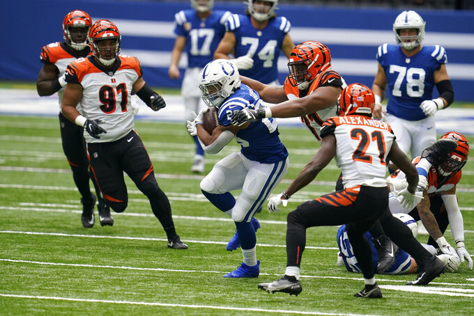 Indianapolis Colts' Jonathan Taylor (28) is tackled by Cincinnati Bengals' Xavier Williams (71) during the first half of an NFL football game, Sunday, Oct. 18, 2020, in Indianapolis. (AP Photo/Michael Conroy)