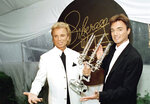 FILE - Illusionists Siegfried Fischbacher, left, and Roy Horn pose after receiving the second annual Liberace Legend Award at a gala benefit in Las Vegas on May 17, 1995. German news agency dpa is reporting that Fischbacher, the surviving member of duo Siegfried & Roy has died in Las Vegas at age 81. The news agency said Thursday that Fischbacher's sister, a nun who lives in Munich, confirmed his death of cancer. Fischbacher's long-time show business partner, Roy Horn, died in May of complications from COVID-19 at a Las Vegas hospital.  (AP Photo/Lennox McLendon, File)