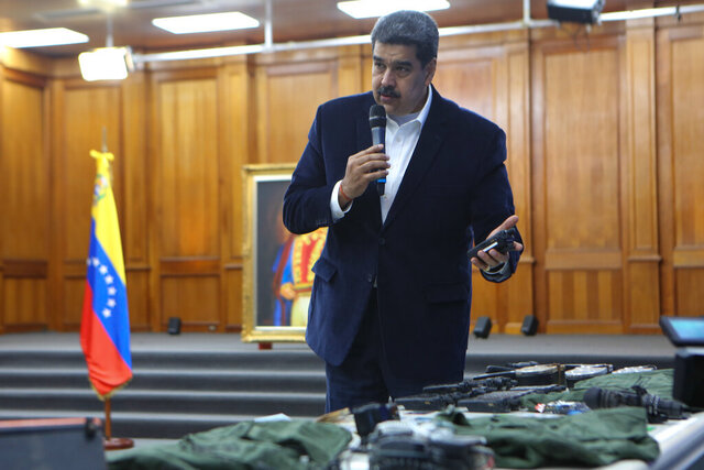 """This photo released by the Venezuelan Miraflores presidential press office shows President Nicolas Maduro speaking over military equipment that he says was seized during an incursion into Venezuela, during his televised address from Miraflores in Caracas, Venezuela, Monday, May 4, 2020. Maduro said authorities arrested two U.S. citizens among a group of """"mercenaries"""" on Monday, a day after a beach raid purportedly aimed at capturing the leader that Venezuelan authorities say they foiled. (Miraflores press office via AP)"""