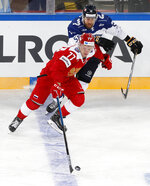 FILE - In this Sunday, Dec. 16, 2018, file photo, Russia's Kirill Kaprizov (77) battles Finland's Jani Hakanpaa (58) during the Channel One Cup ice hockey match in St. Petersburg, Russia. Bonding between veterans and youngsters has been a time-honored tradition in hockey. Older players routinely invite rookies to live with them during their first year. This season, NHL protocols aimed at curbing the spread of COVID-19 could make team-building more difficult. (AP Photo/Dmitri Lovetsky, File)
