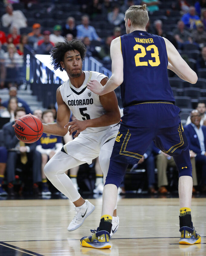 Colorado's D'Shawn Schwartz prepares to pass the ball around California's Connor Vanover during the first half of an NCAA college basketball game in the first round of the Pac-12 men's tournament Wednesday, March 13, 2019, in Las Vegas. (AP Photo/John Locher)