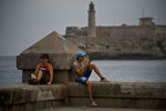 In this Wednesday, Feb. 20, 2019 photo, a man chats using his cellphone next to a woman reading a book while sitting on the seawall in Havana, Cuba. In the 2 1/2 months since Cuba allowed its citizens internet access via cellphones, fast-moving changes are subtle but palpable as Cubans challenge government officials online, post photos of filthy school bathrooms and drag what was once of the world's least-connected countries into the digital age. (AP Photo/Ramon Espinosa)