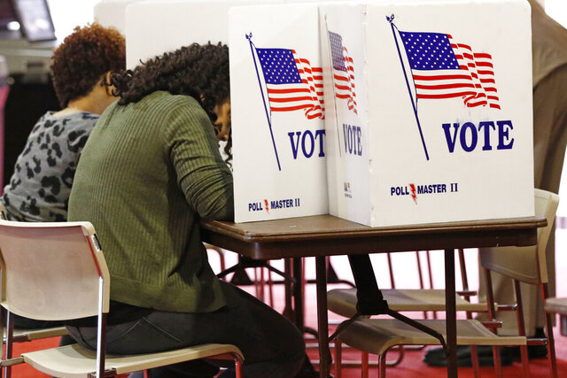 Voters work on their ballots in the kiosks in Jackson, Miss., Tuesday, March 10, 2020. Mississippi is one of several states holding presidential party primaries today. (AP Photo/Rogelio V. Solis)