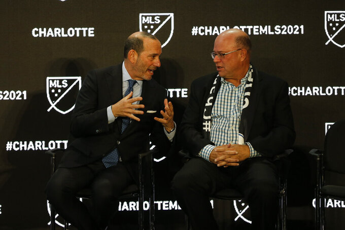 Major League Soccer Commissioner Don Garber, left, and Charlotte MLS owner David Tepper talk during the announcement that an MLS team, owned by Tepper, will begin play Charlotte in 2021 at an event in Charlotte, N.C., Tuesday, Dec. 17, 2019. (AP Photo/Nell Redmond