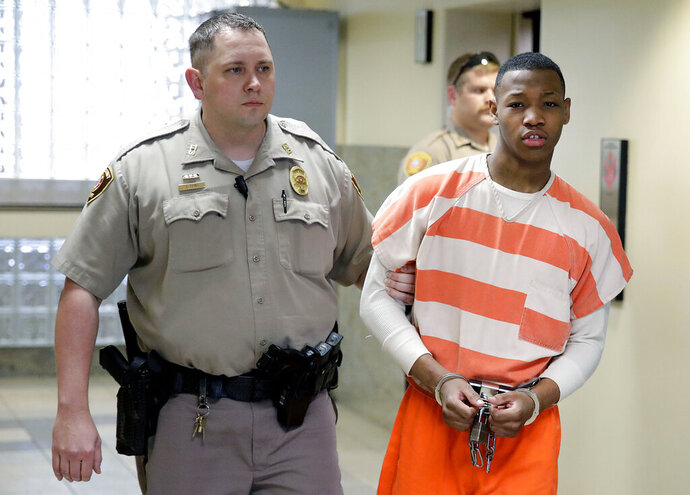 Deonte Green, who was accused of killing a schoolteacher and raping an 81-year-old woman, is escorted into a Tulsa County Courthouse for a sentencing hearing, Tuesday, July 9, 2019, in Tulsa, Okla. Green pleaded guilty in March to first-degree murder and 19 other counts in a blind plea, meaning it was entered without a sentencing agreement with prosecutors. (Mike Simons/Tulsa World via AP)