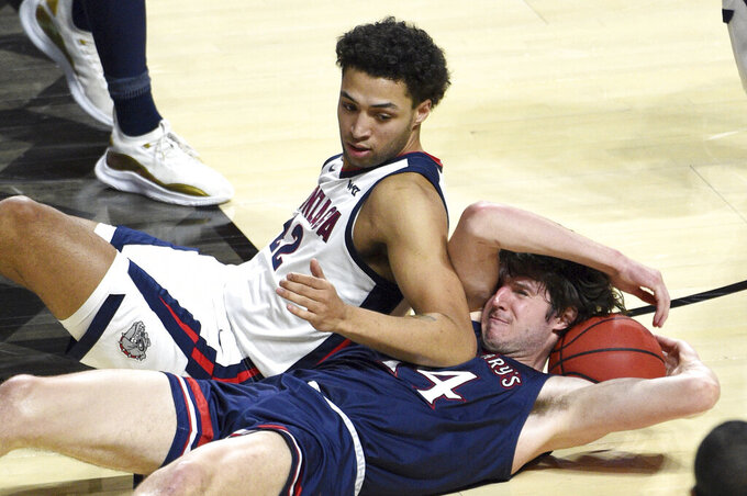Gonzaga forward Anton Watson (22) and Saint Mary's forward Kyle Bowen (14) vie for the ball during the second half of an NCAA semifinal college basketball game at the West Coast Conference tournament Monday, March 8, 2021, in Las Vegas. (AP Photo/David Becker)
