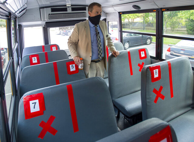 FILE - In this Thursday, July 16, 2020, file photo, Superintendent Keith Perrigan shows the new seating configuration on the school buses for the upcoming school year, in Bristol, Va., where a maximum of 22 students can be on the bus, amid the coronavirus pandemic. (David Crigger/Bristol Herald Courier via AP, File)