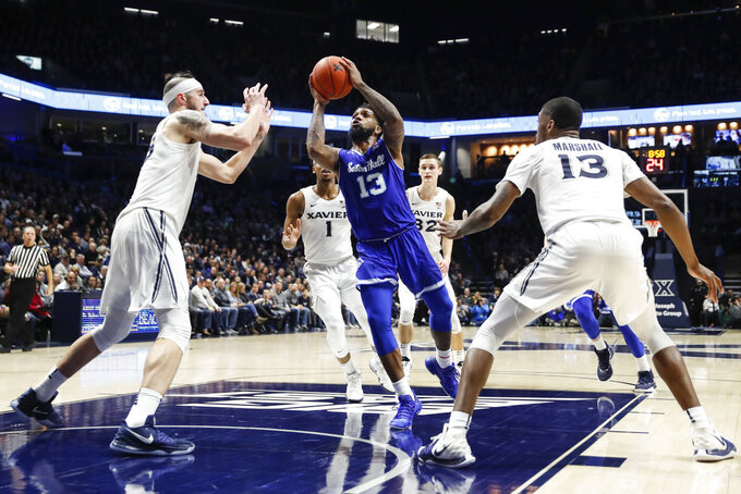 Seton Hall's Myles Powell (13) drives between Xavier's Zach Hankins, left, and Naji Marshall (13) during the second half of an NCAA college basketball game Wednesday, Jan. 2, 2019, in Cincinnati. (AP Photo/John Minchillo)