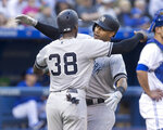 New York Yankees' Aaron Hicks is met at home plate by Cameron Maybin after hitting a three-run home run against the Toronto Blue Jays during the second inning of a baseball game Thursday, June 6, 2019, in Toronto. (Fred Thornhill/The Canadian Press via AP)