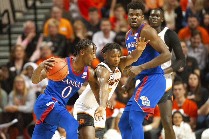 Kansas center Udoka Azubuike, right, watches as Kansas guard Marcus Garrett, left, drives the ball under pressure from Oklahoma State guard Chris Harris Jr. during the first half of an NCAA college basketball game in Stillwater, Okla., Monday, Jan. 27, 2020. (AP Photo/Brody Schmidt)