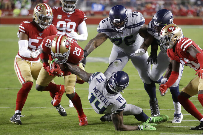 San Francisco 49ers strong safety Jaquiski Tartt (29) strips the ball from Seattle Seahawks wide receiver D.K. Metcalf (14) during the first half of an NFL football game in Santa Clara, Calif., Monday, Nov. 11, 2019. (AP Photo/Ben Margot)