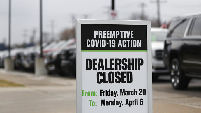 A sign showing an auto dealership closed as a preemptive COVID-19 action is shown Thursday, March 26, 2020 jn Detroit. Automakers' moves to reopen plants in the U.S. come as new auto sales are expected to fall dramatically for the month of March. Edmunds.com expects March sales to fall nearly 36% from a year earlier. (AP Photo/Paul Sancya)