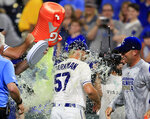 Kansas City Royals starting pitcher Glenn Sparkman (57) is doused by teammate Brian Flynn, left, as Danny Duffy, right, watches following the team's baseball game against the Chicago White Sox at Kauffman Stadium in Kansas City, Mo., Tuesday, July 16, 2019. The Royals won 11-0. (AP Photo/Orlin Wagner)