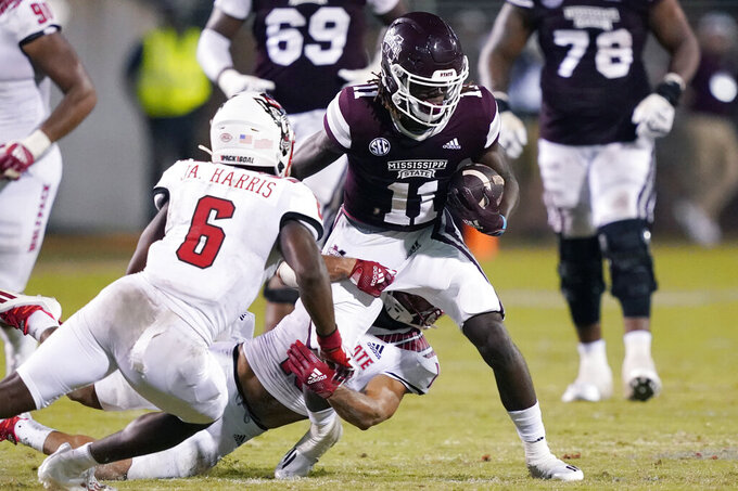 Mississippi State wide receiver Jaden Walley (11) is tackled by North Carolina State defenders during the second half of an NCAA college football game in Starkville, Miss., Saturday, Sept. 11, 2021. (AP Photo/Rogelio V. Solis)