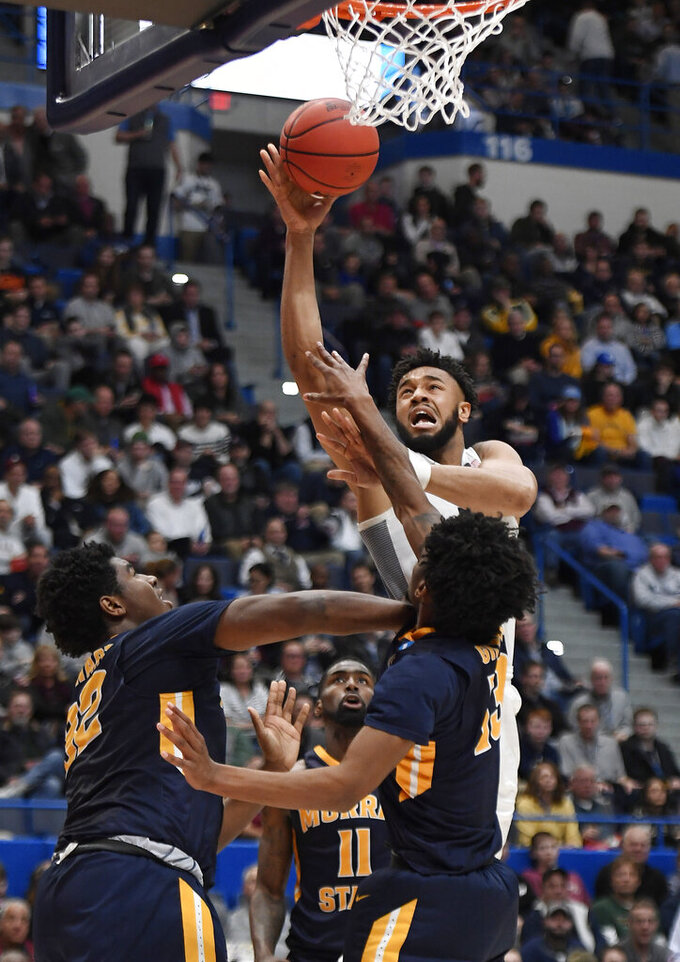 Marquette's Ed Morrow, top, makes a basket while Murray State's Darnell Cowart (32), Shaq Buchanan (11) and Devin Gilmore (13) defend during the first half of a first round men's college basketball game in the NCAA tournament, Thursday, March 21, 2019, in Hartford, Conn. (AP Photo/Jessica Hill)