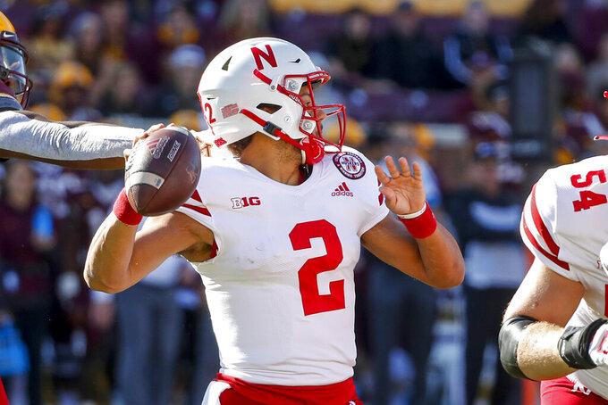 Nebraska quarterback Adrian Martinez (2) passes under pressure from Minnesota during the first quarter of an NCAA college football game Saturday, Oct. 16, 2021, in Minneapolis. (AP Photo/Bruce Kluckhohn)