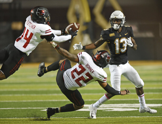 Arkansas State defensive back Antonio Fletcher, left, intercepts a pass intended for Appalachian State wide receiver Christian Horn, right, in the first half of an NCAA college football game, Thursday, Oct. 22, 2020, at Kidd Brewer Stadium in Boone, N.C. (Walt Unks/Winston-Salem Journal via AP)