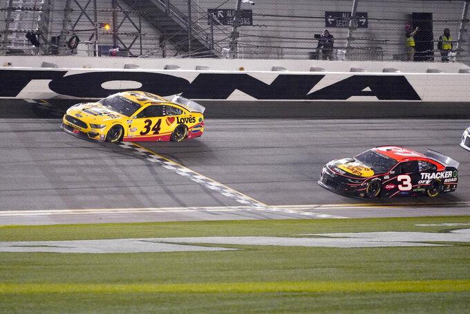 Michael McDowell cruza la línea de meta por delante de Austin Dillon para ganar la carrera Daytona 500 de la NASCAR en el Circuito Internacional de Daytona, el lunes 15 de febrero de 2021 en Daytona Beach, Florida. (AP Foto/John Raoux)