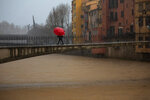 A woman holds an umbrella crossing a bridge over the river Onyar during a storm in Girona, Spain, on Thursday, Jan. 23, 2020. Since Sunday the storm has hit mostly eastern areas of Spain with hail, heavy snow and high winds, while huge waves smashed into towns on the Mediterranean coast and nearby islands of Mallorca and Menorca. (AP Photo/Emilio Morenatti)