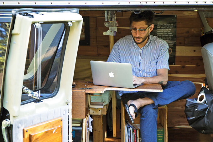 In this 2018 photo, Danny Fenster works out of his van that he made into a home/office in Detroit. A court in Myanmar extended for two weeks the pre-trial detention of Fenster, an American journalist in the military-led Southeast Asian nation who was arrested in May. Fenster was detained at Yangon International Airport on May 24, 2021, as he was about to board a flight to go to the United States to see his family. (Fenster Family photo via AP, File)
