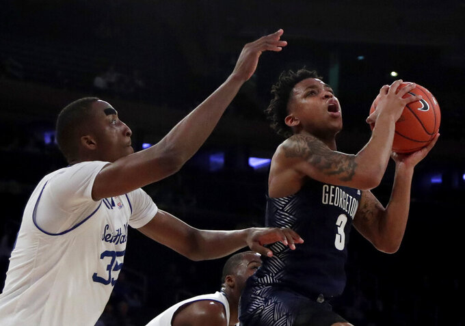 Georgetown guard James Akinjo (3) goes up for a shot against Seton Hall center Romaro Gill (35) during the second half of an NCAA college basketball game in the Big East men's tournament, Thursday, March 14, 2019, in New York. Seton Hall won 73-57. (AP Photo/Julio Cortez)