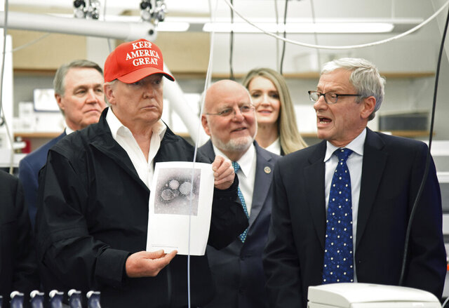 President Donald Trump holds a photograph of coronavirus as Dr. Steve Monroe,right, with CDC speaks to members of the press at the headquarters of the Centers for Disease Control and Prevention in Atlanta on Friday, March 6, 2020. President Trump's trip to the Centers for Disease Control and Prevention, briefly scuttled Friday because of unfounded fears that someone there had contracted the coronavirus, was back on, giving the president another chance to calm growing alarm about the spread of the virus in America.  (Hyosub Shin/Atlanta Journal-Constitution via AP)