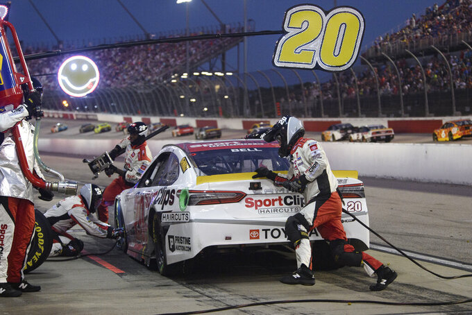 Crew members work on the car driven by Christopher Bell during a pit stop in a NASCAR Cup Series auto race Sunday, Sept. 5, 2021, in Darlington, S.C. (AP Photo/John Amis)