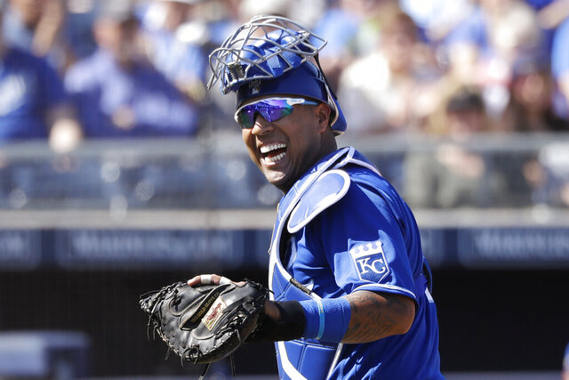 FILE - In this Wednesday, March 4, 2020, file photo, Kansas City Royals catcher Salvador Perez smiles as he turns to a teammate who made an out on a difficult play against the San Diego Padres in the first inning during a spring training baseball game in Peoria, Ariz. (AP Photo/Elaine Thompson, File)