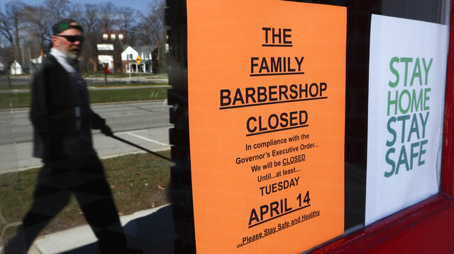 A pedestrian walks by The Family Barbershop, closed due to a Gov. Gretchen Whitmer executive order, in Grosse Pointe Woods, Mich., Thursday, April 2, 2020. The coronavirus COVID-19 outbreak has triggered a stunning collapse in the U.S. workforce with millions of people losing their jobs in the past two weeks and economists warn unemployment could reach levels not seen since the Depression, as the economic damage from the crisis piles up around the world. (AP Photo/Paul Sancya)