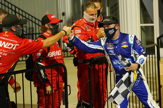 Justin Allgaier, right, greets his crew in Victory Lane as he celebrates after winning a NASCAR Xfinity Series auto race Friday, Sept. 11, 2020, in Richmond, Va. (AP Photo/Steve Helber)